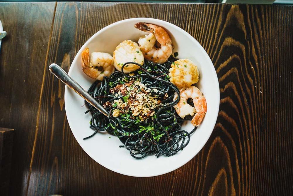 Scallops and prawns over black spaghetti, Roadhouse, Smithers, British Columbia.