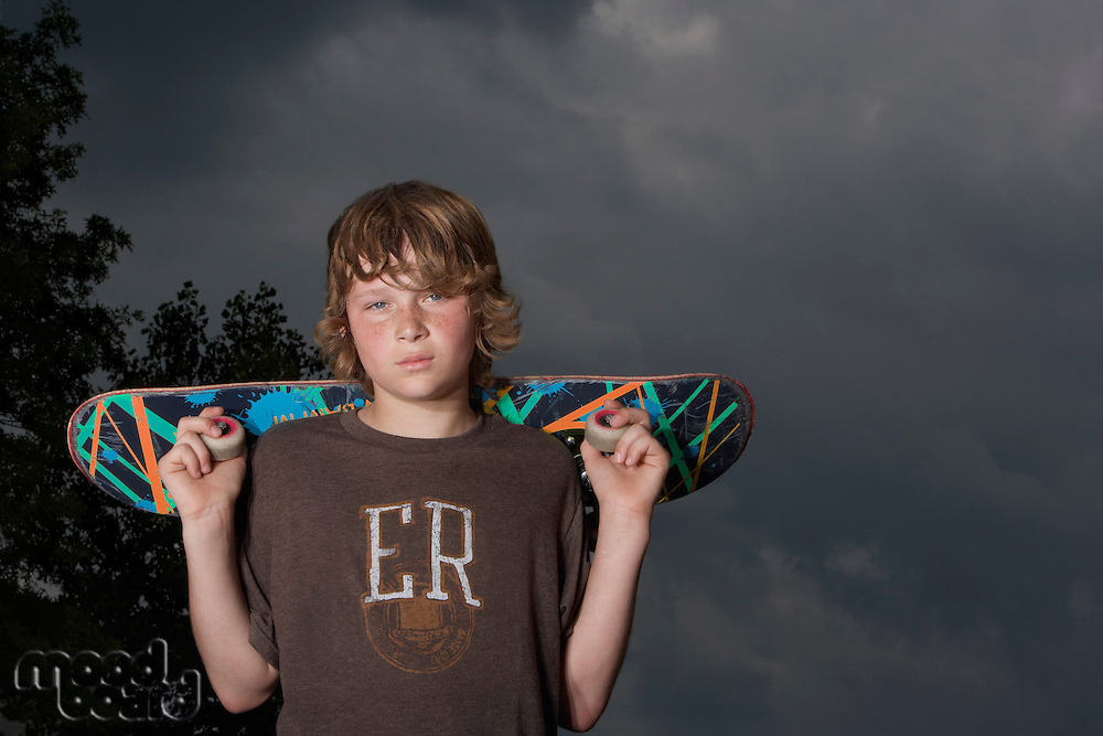 Teenage boy (13-15) holding skateboard outdoors portrait low angle view