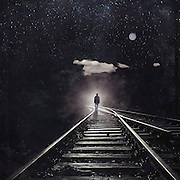 Surreal photomanipulation with a man walking a railroad towards an ominous light.<br />