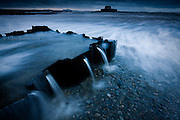 Nominated in 10th (2017) International Colour Awards (Fine Art category) <br /> <br /> Field drainage water pours out through a water channel into the Irish Sea here at Porth Cwyfan. The 13th Century, Eglwys Cwyfan (St Cwyfan's Church), not far from the small village of Aberffraw on Anglesey's West coast, at one time stood on the mainland coast but over the years, the sea has eroded the surrounding land leaving it stranded on it's own little island. Services are still occasionally held here but times are tide dependent.