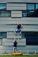 Two male climbers as seen venturing up a wall of an office building of University of Groningen on a Summer afternoon.