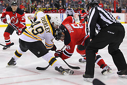 Jan 4, 2012; Newark, NJ, USA; Boston Bruins right wing Rich Peverley (49) and New Jersey Devils right wing Dainius Zubrus (8) face-off during the second period at the Prudential Center.