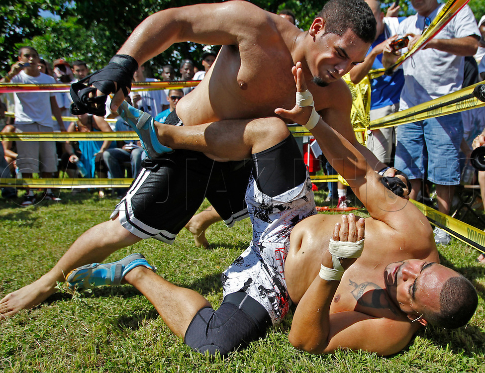 "These are fighters, Yan Rugel, top, and Michael Gibson on September 18, 2010. Dhafir Harris, ""Dada 5000"", puts on backyard fights at his mother house, which go viral on youtube and have been the subject of documentaries. Sometimes the men fight until they are unconscious. There' s no gloves and occasionally, there's a cage. The community has taken to the events, because they are able to set up businesses selling food and washing cars."