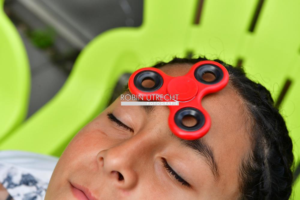 rotterdam - spelen met fidget spinners, een klein tolletje dat je moet laten draaien tussen duim en wijsvinger of op de neus. Het speeltje zou kinderen met de aandachtsstoornis ADHD helpen te ontspannen.  A child plays with the currently popular, supposedly stress-relieving toy known as a 'fidget spinner' in copyright robin utrecht