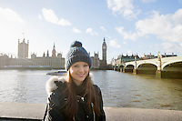 Portrait of beautiful young woman standing by river Thames; London; UK