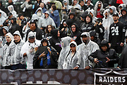 Oakland Raiders fans wear rain gear on a rainy day during the 2016 NFL week 6 regular season football game against the Kansas City Chiefs on Sunday, Oct. 16, 2016 in Oakland, Calif. The Chiefs won the game 26-10. (©Paul Anthony Spinelli)