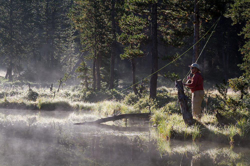 A fly fisherman prepares to cast on a calm backcountry lake early in the morning as the mist rises.