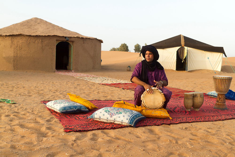 M'HAMID EL GHIZLANE, MOROCCO - 26th April 2014 - Musician plays drums at a camp in the Erg Chigaga region of the Moroccan Sahara, beyond M'Hamid el Ghizlane, Erg Chigaga, Southern Morocco.