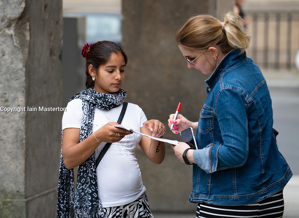 Tourist signing fake petition before handing over money donation in common scam operated by gangs of women in Berlin, Germany