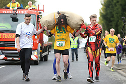 © Licensed to London News Pictures. 17/04/2017. Gawthorpe UK. UK. Competitor JOEL HICKS is given assistance while carrying a huge load in the mens race of The World Coal Carrying Championships in the village of Gawthorpe in Yorkshire. Every year Men & women carry huge sacks of coal from the Royal Oak Pub in Ossett 1012 metres to the finish line at the Maypole Green in the village of Gawthorpe. Photo credit: Andrew McCaren/LNP