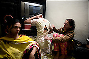 "Nadia (on the left), 21 years old, Chabbo (in the middle), 32 years old, and Sery (on the right), 29 years old, all transvestites at their  common apartment. Evening in Lahore, Pakistan on Monday, December 01 2008.....""Not men nor women"". Just Hijira, Kusra. Painted lips, Kajal surrounding their eyes and colourful veils..Pakistan is today considered a strongly, foundamentalist as well, islamic country. But under its reputation, above all over the talebans' continuos advancing, stirs a completely extraneous world, a multiethnic mixed society. Transvestites make part of it, despite this would not be admitted by a strict law. Third gender, the Hijira are born as men (often ermaphrodites) or with an ambiguous genital situation, and they have their testicles and penis removed through a - often brutal - surgical operation. The peculiarity is that this operation does not contemplate the reconstruction of a female organ. This is the reason why they are not considered as men nor women, just Hijira. They are often discriminated, persecuted  and taxed with being men prostitutes in the muslim areas. The members of this chast perform dances during celebrations, especially during weddings, since it is anciently believed that an EUNUCO's dance and kiss in the wedding day brings good luck to the couple's fertility...To protect the identities of the recorded subjects names and specific .places are fictionals."