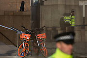 The morning after the terrorist attack at Fishmongers Hall on London Bridge, in which Usman Khan (a convicted, freed terrorist) killed 2 during a knife a attack, then subsequently tackled by passers-by and shot by armed police - officers guard the southern end of the bridge where a rental bike has been abandoned during the evacuation, on 30th November 2019, in London, England.