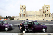 A taxi driver takes advantage of the fact of not having customers to clean his London alike cab, in front of the House of Government building. Azeri GDP grew 41.7% in the first quarter of 2007, possibly the highest of any nation worldwide, as the country economy completed its post-Soviet transition into a major oil based economy.<br />