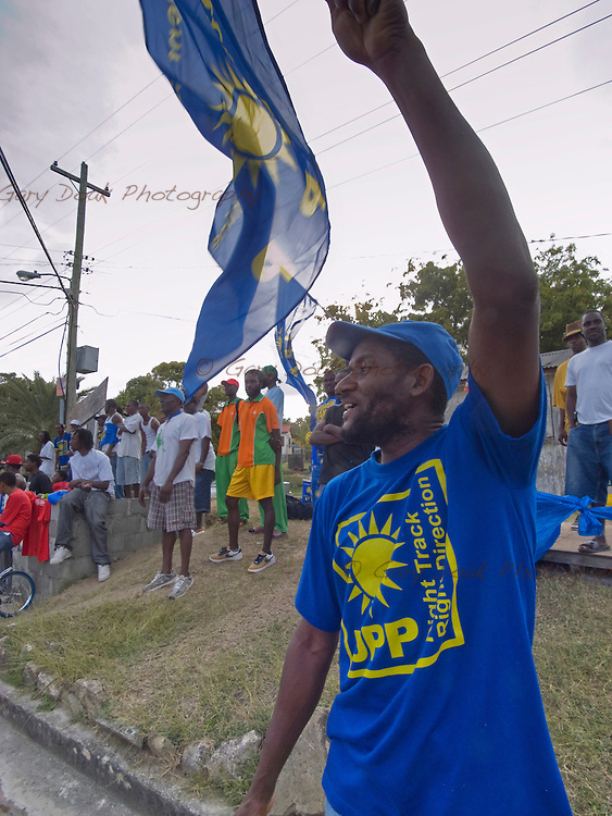 A United Progressive Party (UPP) supporter waves his flag at Antigua Labour Party supporters on their way to a party political rally, Antigua