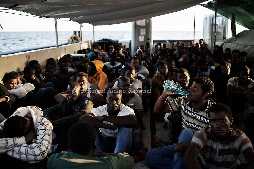 Italy: MSF Dignity1: African migrants rescued at sea sit down on the main deck of the Dignity1 on August 23, 2015. Alessio Romenzi