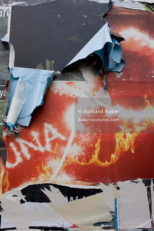 Paper sheets and layers of mixed advertising media campaigns are peeling on a south London billboard.