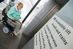 Woman wheelchair user entering accessible lift to access train station from tram stop,
