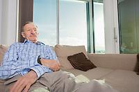 Senior man relaxing on sofa at home