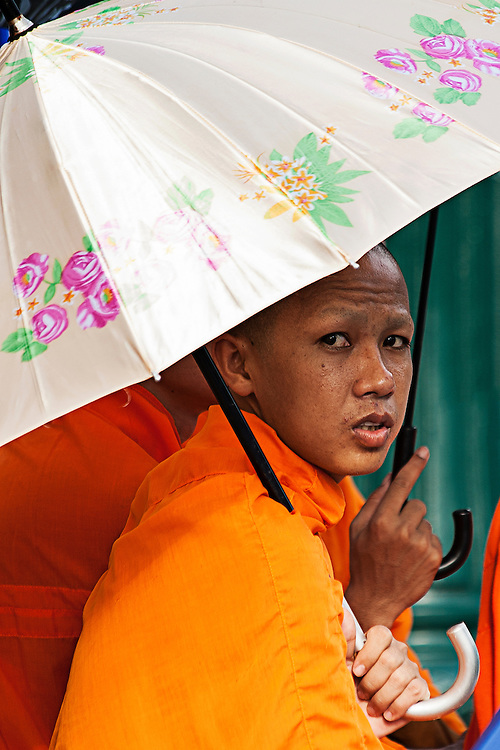 A Buddhist monk sheltering under an umbrella while waiting for the funeral parage of King