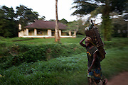 A woman carrying fruit and vegetables passes a residential home in Yangambi, DR Congo, on Friday, Dec. 5, 2008. The station contains 250 residential homes, some are derelict but most are inhabited by more than one family. These are usually workers at the facility who are assigned the homes by the Ministry of Agriculture in Kinshasa..Yangambi Research Station is the former Belgian headquarters for all major scientific ecological, biological and agricultural research in Africa between the 1930's and 1960. Abandonment began in 1960 with independence and although the Congolese attempted to maintain Yangambi, sometimes in co-operation with the Belgians, the facility began to fall into disrepair through the 70's and 80's. War in the 1990's halted all potential for progress and for the past decade a skeleton crew has made a futile attempt to stave off further decline.