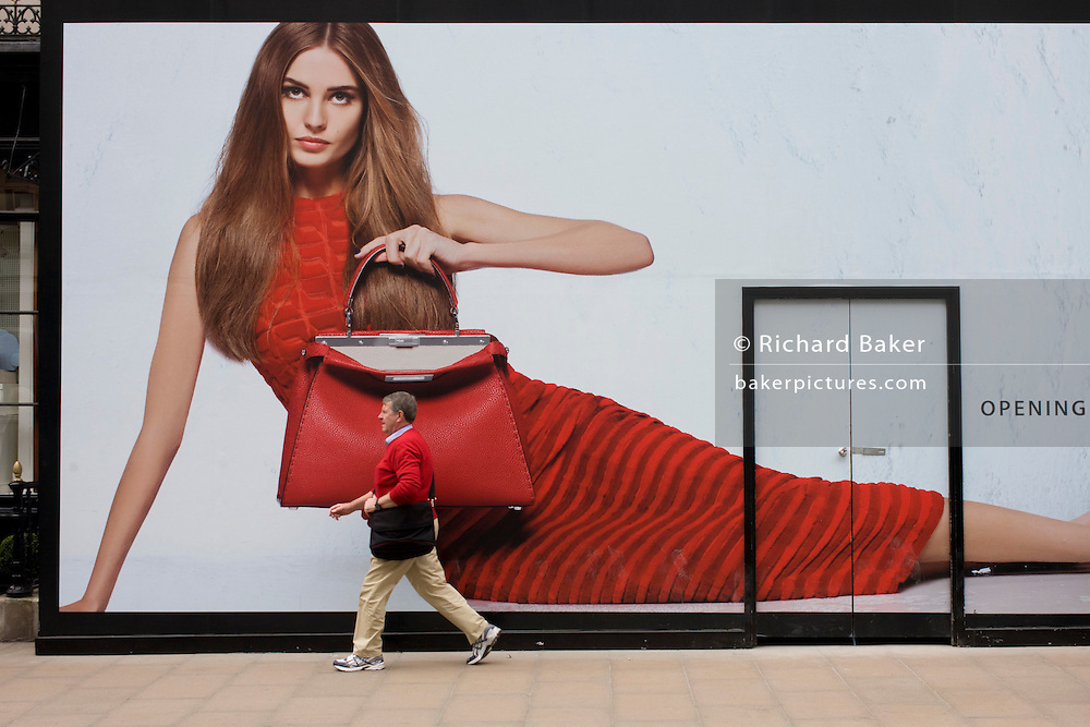 Male shopper walks past a womens' bag accessory retailer hoarding in Bond Street, London.
