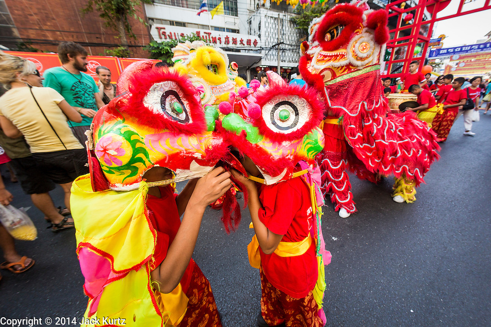 31 JANUARY 2014 - BANGKOK, THAILAND:   Members of a children's Chinese Lion dance troupe perform on Yaowarat Road during Lunar New Year festivities, also know as Tet and Chinese New Year, in Bangkok. This year is the Year of the Horse. The Lion Dance scares away evil spirits and brings prosperity and luck. Ethnic Chinese make up about 14% of Thailand and Chinese holidays are widely celebrated in Thailand.     PHOTO BY JACK KURTZ