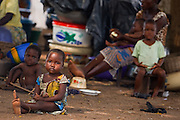A child sits on the ground in a spontaneous settlement near the village of Kpoto, Benin on Tuesday October 26, 2010. About 1500 people have settled here after their village was almost entirely destroyed by floods that have hit Benin over the past few weeks. Almost all of the village's 1500 people have moved to a location near the local church, located about 500 meters away, where they now live in basic shelters.