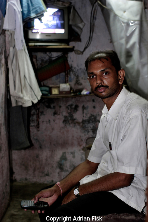 Anwar Shaikh sits in the room that serves as his home. On average most homes in Dharavi are one room of about 125 square feet. Lavatory blocks exist but one lavatory per 100 people, washing the body is done in the alleys outside of the homes.