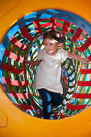 Young girl climbs through netted tunnel in soft play centre