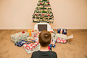 young boy looks at the Christmas presents under an ecological, reusable Christmas tree