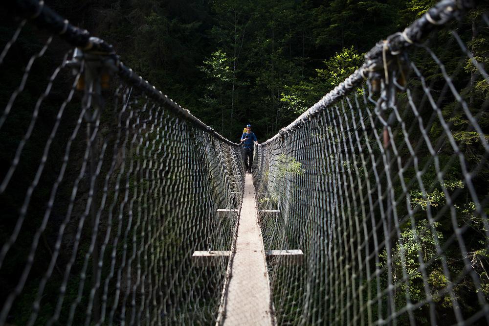 Zach Podell-Eberhardt crosses the suspension footbridge across Logan Creek, West Coast Trail, British Columbia, Canada.