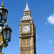 Big Ben with Street Lights and Blue Sky Copyspace 169-095109613 The clock of Elizabeth Tower (commonly known as Big Ben) on the Palace of Westminster, with some of the ornate streets lights of Westminster Bridge in the foreground. Includes copyspace.