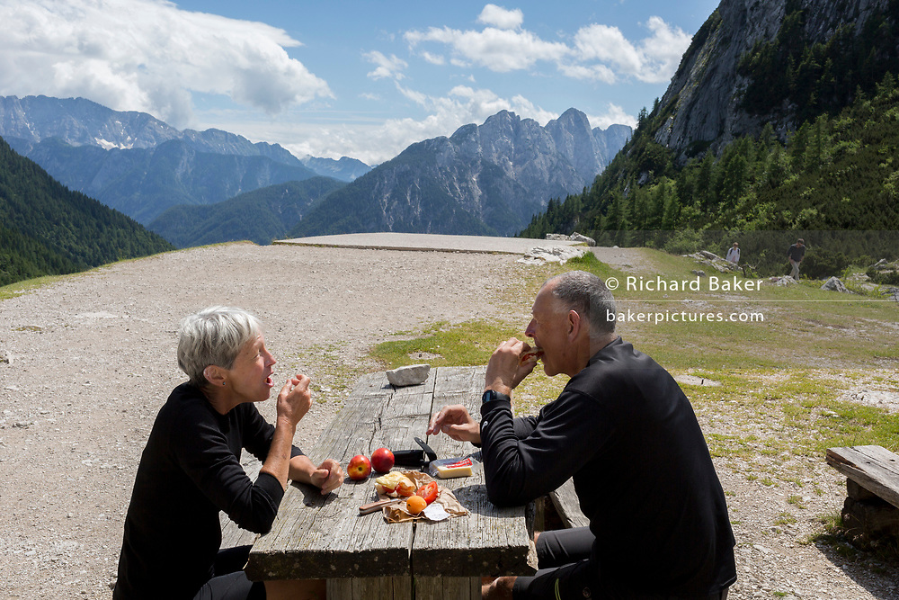 Two cyclists eat lunch at the top of Vrsic Pass in the Slovenian Julian Alps, on 22nd June 2018, in Triglav National Park, Slovenia.