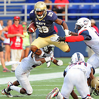 10 September 2016:   Navy Midshipmen running back Darryl Bonner (29) leaps over the tackle of Connecticut Huskies cornerback Jamar Summers (21) at the Navy Marine Corps Stadium in Annapolis, MD. where the Navy Midshipmen defeated the Connecticut Huskies 28-24.