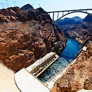 Looking down from the top of the massive concrete wall of the Hoover Dam. At the very top of frame is the Mike O'Callaghan – Pat Tillman Memorial Bridge. In the middle is the outflow of the Colorado River with the twin buildings housing the hydroelectric turbines on either side of the river. The dam spans the state border, with Arizona on the left and Nevada on the right. The supports attached to the rock wall are leaning so as to keep the electricity cables away from the rock to prevent them from shorting out.