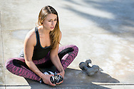 Girl stretching on pavement with dumbbells.