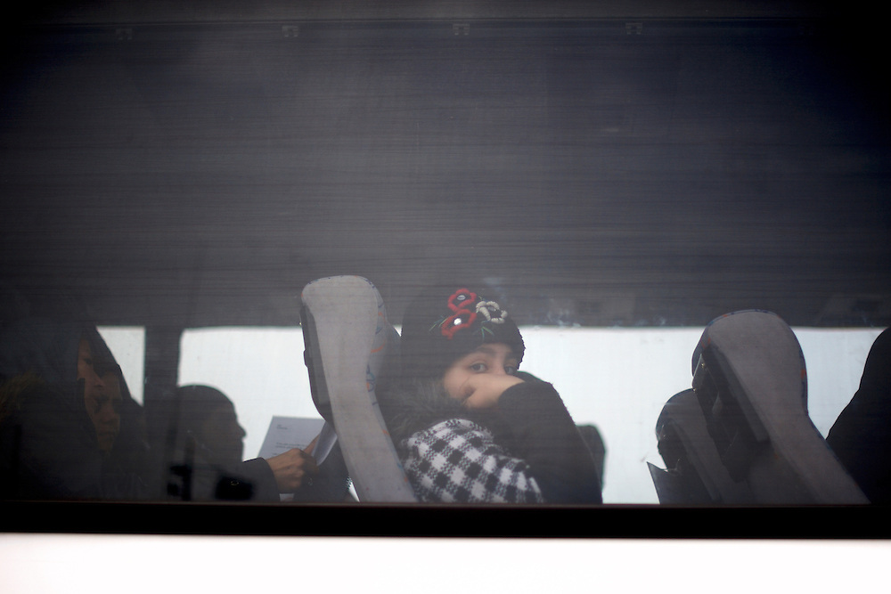 A child is seen inside a UNHCR bus in Mytilene port, minutes before been driven to a registration centre in Moira, Lesbos island.