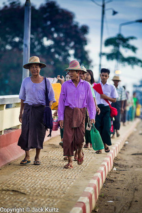 Burmese walk into Pantanaw, a town in the Irrawaddy Delta (or Ayeyarwady Delta) in Myanmar. The region is Myanmar's largest rice producer, so its infrastructure of road transportation has been greatly developed during the 1990s and 2000s. Two thirds of the total arable land is under rice cultivation with a yield of about 2,000-2,500 kg per hectare. FIshing and aquaculture are also important economically. Because of the number of rivers and canals that crisscross the Delta, steamship service is widely available.