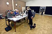 Nederland, Ubbergen, 19-11-2014Stemmen tijdens de tussentijdse verkiezingen voor de gemeenteraad. In deze tussentijdse verkiezingen vanwege gemeentelijke herindeling en fusies kan in Beek-Ubbergen, Millingen  aan de Rijn en Groesbeek ook gestemd worden middels een referendum over de nieuwe naam van de gemeente. Vrouw is echtgenote van fotograaf. Stembureau, stemburo in een buurthuis. Netherlands, elections voting . Polling station Foto: Flip Franssen
