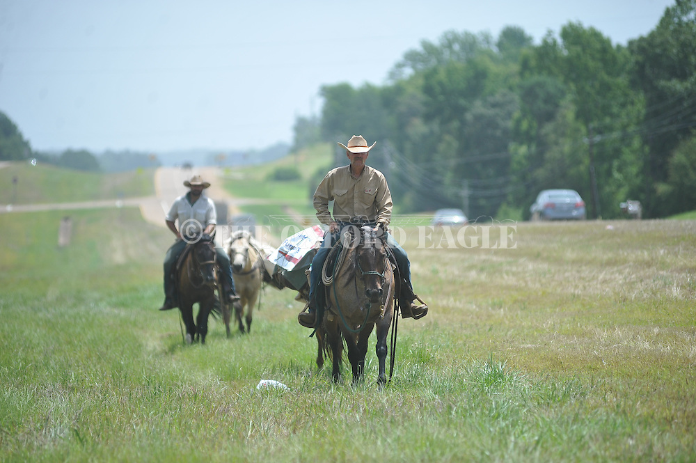 Raymond Avery (foreground) and Matt Littrell ride horses along Highway 6 in Oxford, Miss. on Tuesday, July 1, 2014. Littrell is a former U.S. Marine who is riding cross country to raise money for wounded veterans.