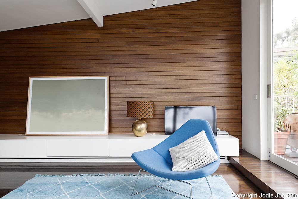 Horizontal wood panelling and blue occasional chair in mid century modern iving room
