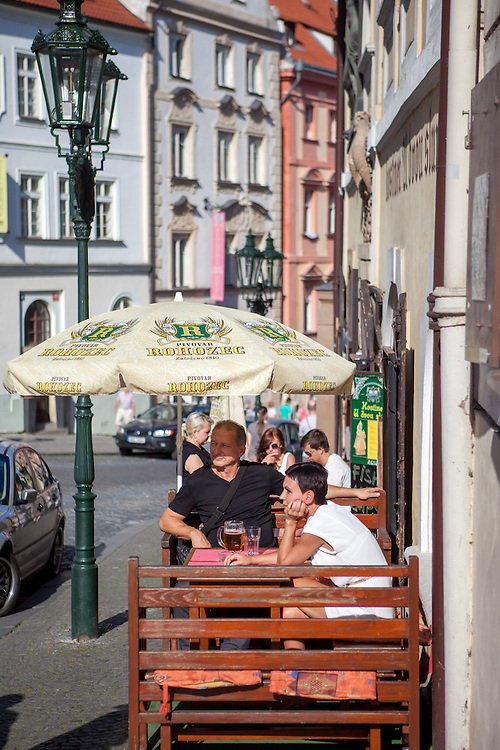 Natives and tourist are sitting in a pub at Nerudova street which is leading from Prague Castle to Malostranska Square.