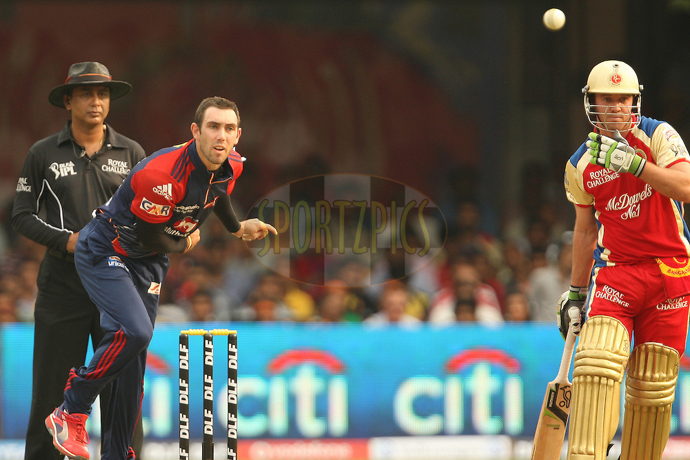 Glenn Maxwell in his delivery stride with AB de Villiers looking on during match 5 of the the Indian Premier League ( IPL) 2012  between The Royal Challengers Bangalore and the Delhi Daredevils  held at the M. Chinnaswamy Stadium, Bengaluru on the 7th April 2012..Photo by Jacques Rossouw/IPL/SPORTZPICS