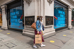 © Licensed to London News Pictures. 28/07/2020. LONDON, UK. Shoppers outside Selfridges' flagship store on Oxford Street.  Selfridges has announced that staff numbers will be reduced by 450 (14% of the total headcount) as annual sales are expected to be significantly less than the prior year.  The coronavirus pandemic and general downturn in the retail industry are cited  as the main reasons for the job cuts..  Photo credit: Stephen Chung/LNP
