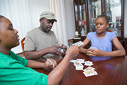 Father playing a game of cards with his teenage daughter and son,