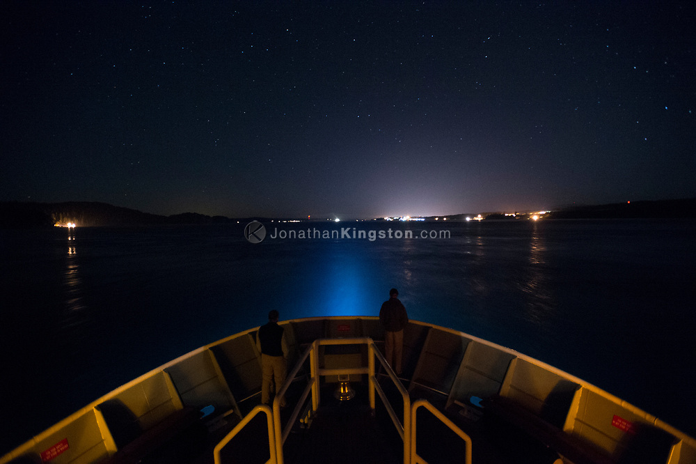 The bow of a small cruise ship sailing under a starry sky near Campbell River, British Columbia, Canada.