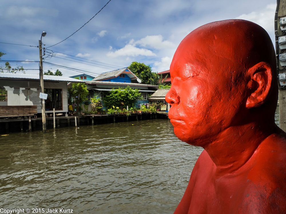 "27 JUNE 2015 - BANGKOK, THAILAND:   Statue of a man sitting on a dock at the ""Artists' House"" on Khlong Bang Luang. The Bang Luang neighborhood lines Khlong (Canal) Bang Luang in the Thonburi section of Bangkok on the west side of Chao Phraya River. It was established in the late 18th Century by King Taksin the Great after the Burmese sacked the Siamese capital of Ayutthaya. The neighborhood, like most of Thonburi, is relatively undeveloped and still criss crossed by the canals which once made Bangkok famous. It's now a popular day trip from central Bangkok and offers a glimpse into what the city used to be like.       PHOTO BY JACK KURTZ"