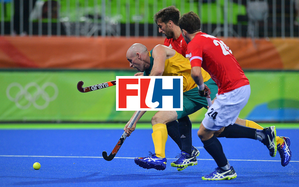 Australia's Glenn Turner  (L), Britain's Iain Lewers (R) and Britain's Adam Dixon chase the ball during the men's field hockey Britain vs Australia match of the Rio 2016 Olympics Games at the Olympic Hockey Centre in Rio de Janeiro on August, 10 2016. / AFP / Carl DE SOUZA        (Photo credit should read CARL DE SOUZA/AFP/Getty Images)