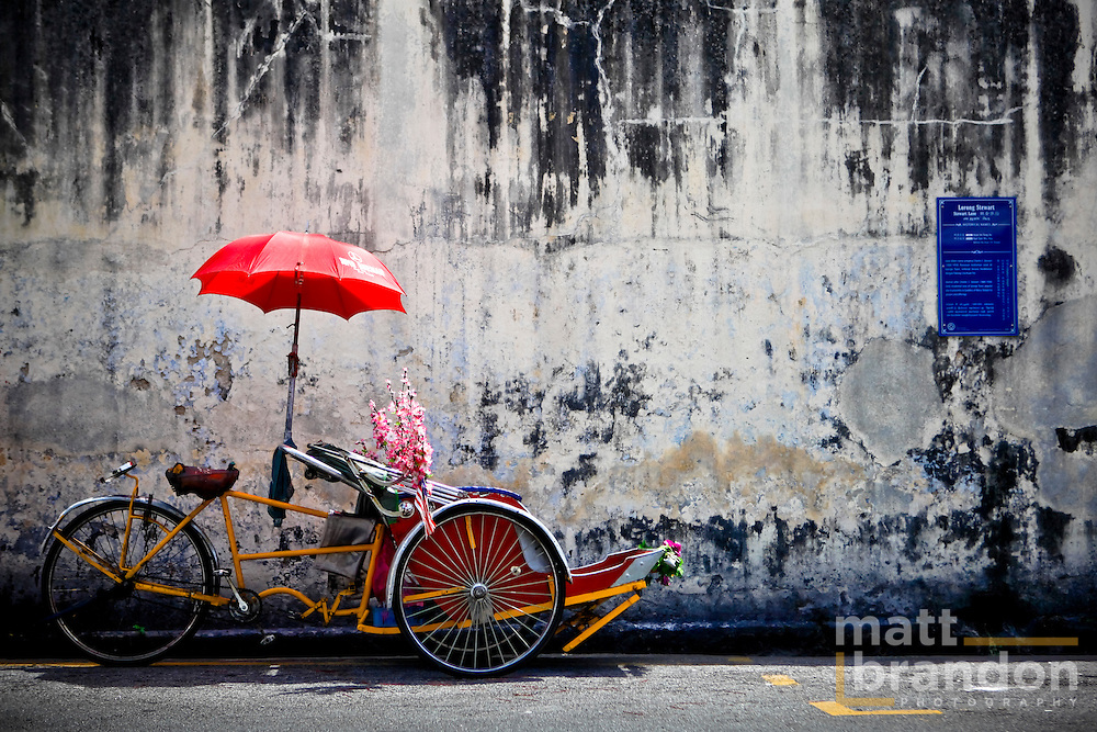 A traditional Penang trishaw sits in front of an old weathered wall.