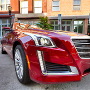 Brand new red 2015 Cadillac CTS luxury sedan, parked on Delaware Street in downtown Kansas City's River Market area.